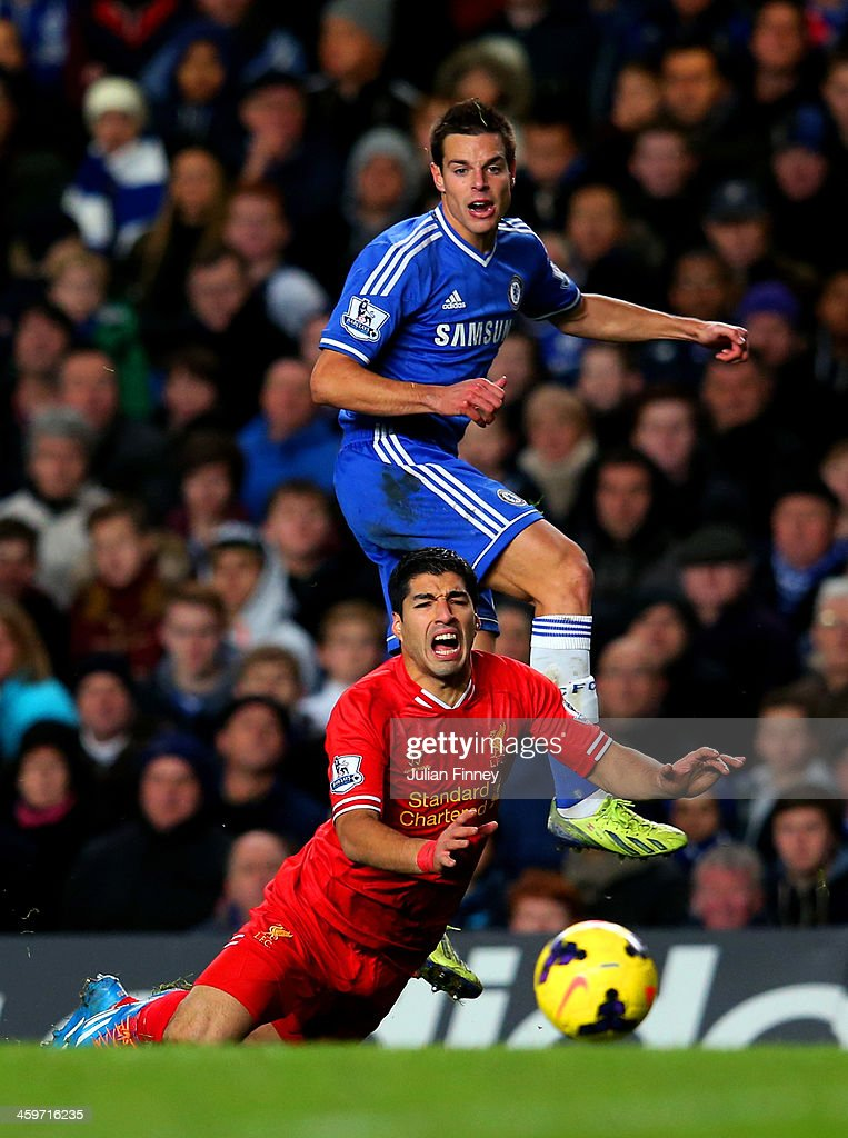 Luis Suarez of Liverpool goes to ground after the challenge from Cesar Azpilicueta of Chelsea during the Barclays Premier League match between Chelsea and Liverpool at Stamford Bridge on December 29, 2013 in London, England.