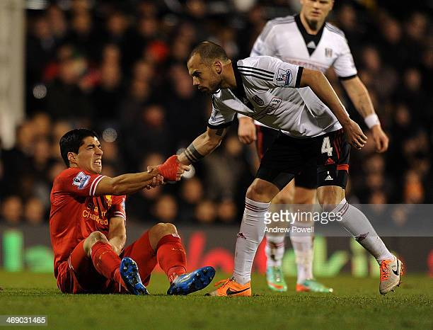 Luis Suarez of Liverpool help up after a foul by John Heitinga of Fulham during the Barclays Premier Leauge match between Fulham and Liverpool at...