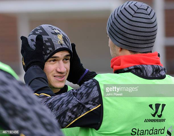 Luis Suarez of Liverpool helps Philippe Coutinho with his hat during a training session at Melwood Training Ground on February 6 2014 in Liverpool...