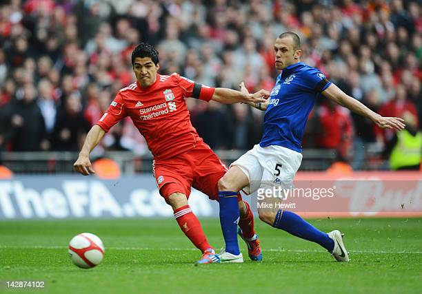 Luis Suarez of Liverpool holds off John Heitinga of Everton to score their first goal during the FA Cup with Budweiser Semi Final match between...