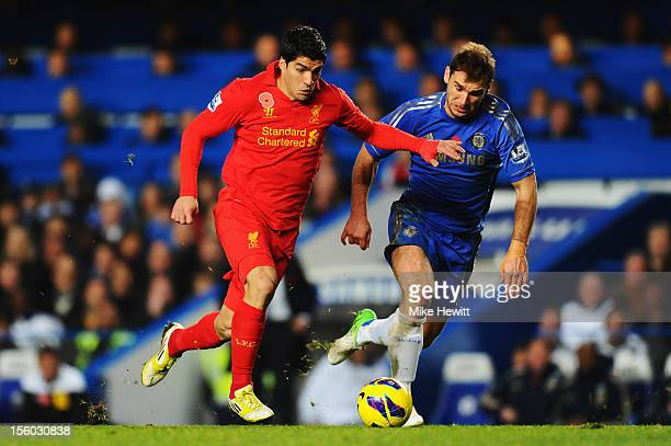 Luis Suarez of Liverpool holds off the challenge of Branislav Ivanovic of Chelsea during the Barclays Premier League match between Chelsea and...