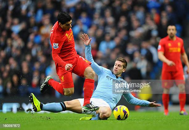Luis Suarez of Liverpool hurdles the challenge of Matija Nastasic of Manchester City during the Barclays Premier League match between Manchester City...