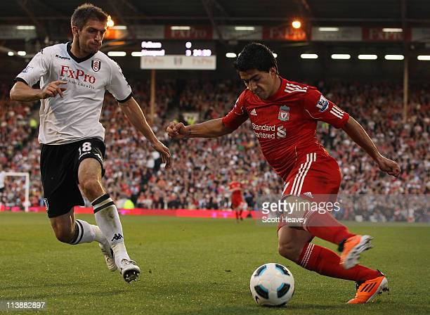 Luis Suarez of Liverpool is challenged by Aaron Hughes of Fulham during the Barclays Premier League match between Fulham and Liverpool at Craven...