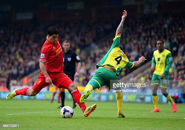Luis Suarez of Liverpool is challenged by Bradley Johnson of Norwich City during the Barclays Premier League match between Norwich City and Liverpool...