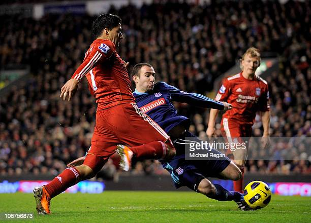 Luis Suarez of Liverpool is challenged by Danny Higginbotham of Stoke City during the Barclays Premier League match between Liverpool and Stoke City...
