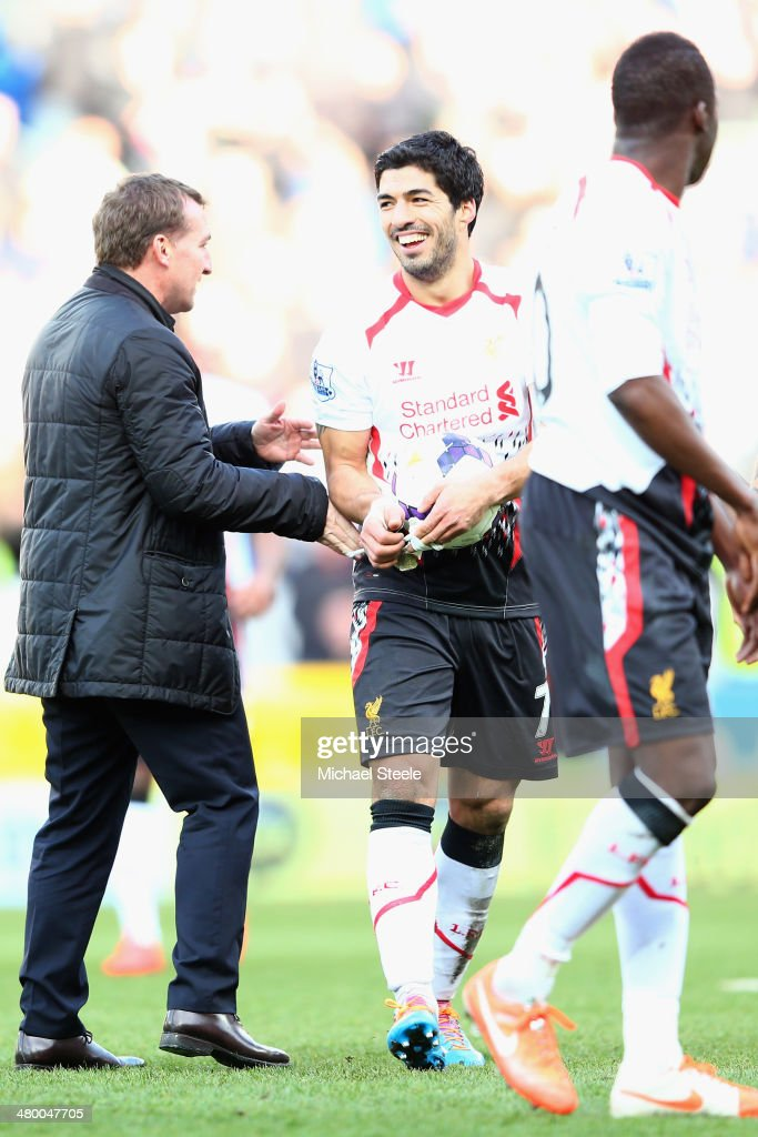 Luis Suarez (C) of Liverpool is congratulated by his manager Brendan Rodgers (L) at the final whistle after scoring a hat trick during his teams 6-3 victory during the Barclays Premier League match between Cardiff City and Liverpool at the Cardiff City Stadium on March 22, 2014 in Cardiff, Wales.