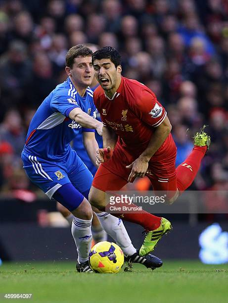 Luis Suarez of Liverpool is fouled during the Barclays Premier League match between Liverpool and Hull City at Anfield on January 1 2014 in Liverpool...