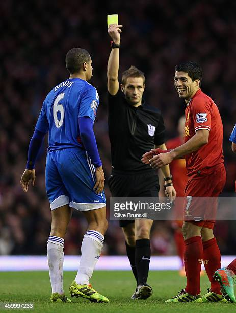 Luis Suarez of Liverpool is shown the yellow card by match referee Mr C Pawson as Curtis Davies of Hull City looks on during the Barclays Premier...