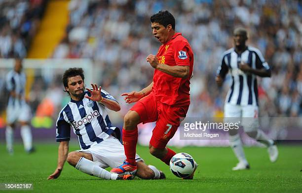 Luis Suarez of Liverpool is tackled by Claudio Yacob of West Brom during the Barclays Premier League match between West Bromwich Albion and Liverpool...