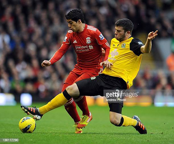 Luis Suarez of Liverpool is tackled by Grant Hanley of Blackburn during the Barclays Premier League match between Liverpool and Blackburn Rovers at...