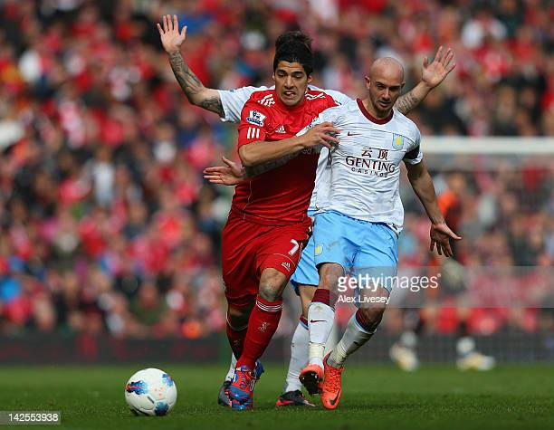 Luis Suarez of Liverpool is tackled by Stephen Ireland of Aston Villa during the Barclays Premier League match between Liverpool and Aston Villa at...
