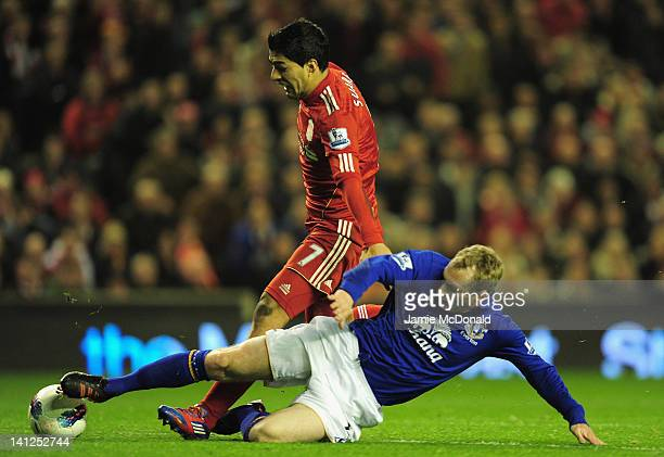 Luis Suarez of Liverpool is tackled by Tony Hibbert of Everton during the Barclays Premier League match between Liverpool and Everton at Anfield on...