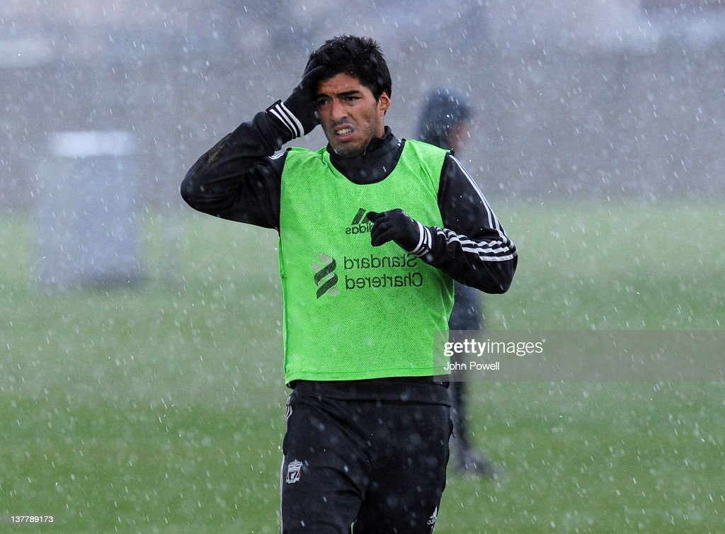 Luis Suarez of Liverpool looks unhappy as he is caught in a hail storm during a team training session at Melwood Training Ground on January 27, 2012 in Liverpool, England.