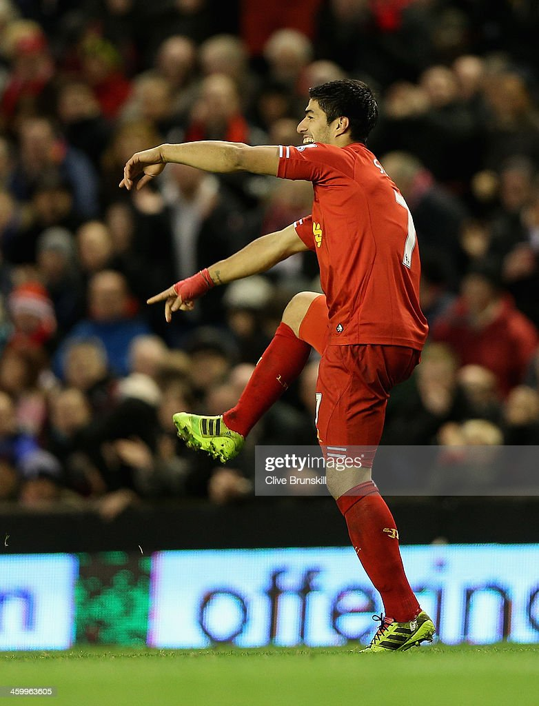 Luis Suarez of Liverpool points to his boot after scoring the second goal from a free kick during the Barclays Premier League match between Liverpool and Hull City at Anfield on January 1, 2014 in Liverpool, England.