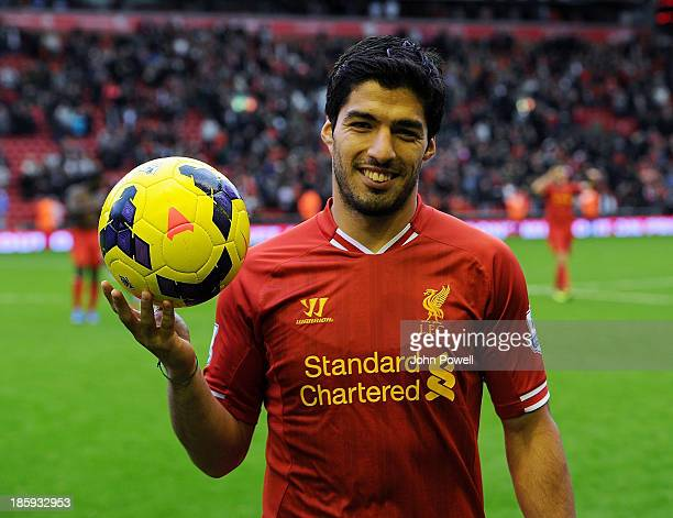 Luis Suarez of Liverpool poses with the match ball after scoring a hat trick at the end of the Barclays Premier League match between Liverpool and...