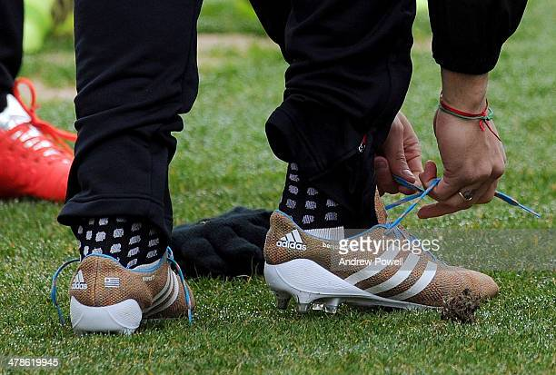 Luis Suarez of Liverpool puts his new knitted boots on before a training session at Melwood Training Ground on March 14, 2014 in Liverpool, England.