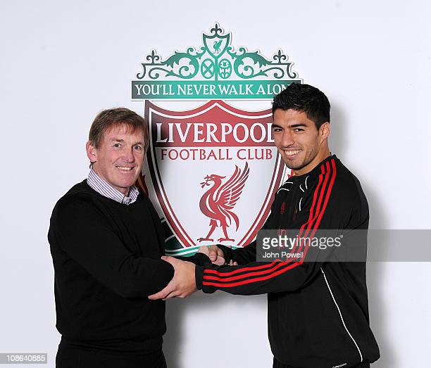 Luis Suarez of Liverpool shakes hands with Kenny Dalglish manager of Liverpool at Melwood training ground on January 29 2011 in Liverpool England