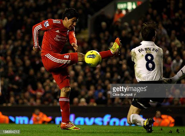 Luis Suarez of Liverpool shoots and misses under pressure from Scott Parker of Tottenham Hotspur during the Barclays Premier League match between...