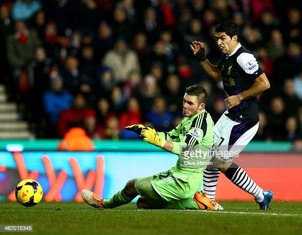 Luis Suarez of Liverpool shoots past Jack Butland of Stoke City to score their second goal during the Barclays Premier League match between Stoke...