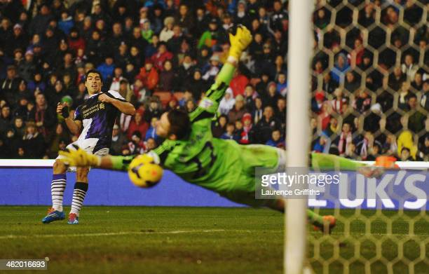 Luis Suarez of Liverpool shoots past Jack Butland of Stoke City to score their fourth goal during the Barclays Premier League match between Stoke...