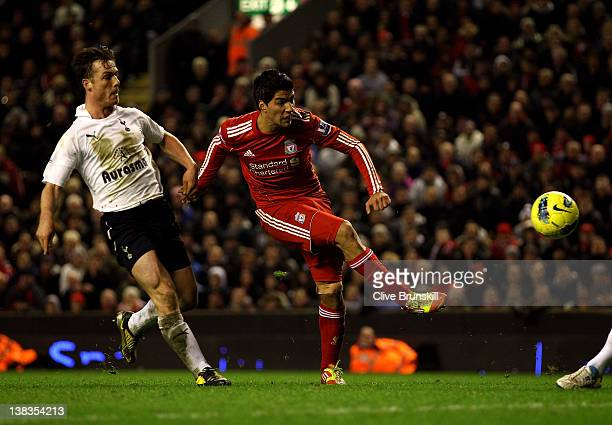 Luis Suarez of Liverpool shoots under pressure from Scott Parker of Tottenham Hotspur during the Barclays Premier League match between Liverpool and...