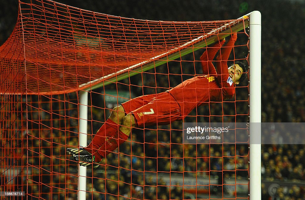 Luis Suarez of Liverpool swings on the cross bar following a missed chance during the Barclays Premier League match between Liverpool and Sunderland at Anfield on January 2, 2013 in Liverpool, England.