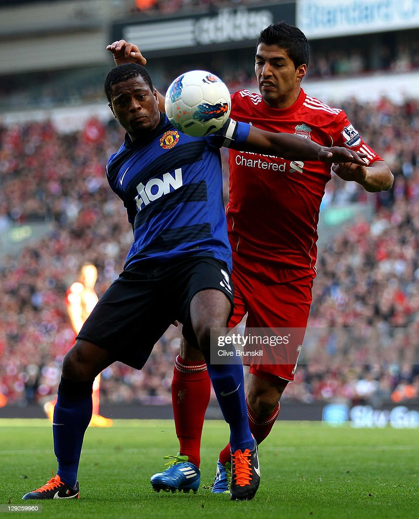 Luis Suarez of Liverpool tussles for posesssion with Patrice Evra of Manchester United during the Barclays Premier League match between Liverpool and Manchester United at Anfield on October 15, 2011 in Liverpool, England.