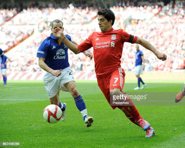 Luis Suarez of Liverpool with Leon Osman of Everton in action during the FA Cup Semi Final match at Wembley Stadium on April 14 2012 in London England