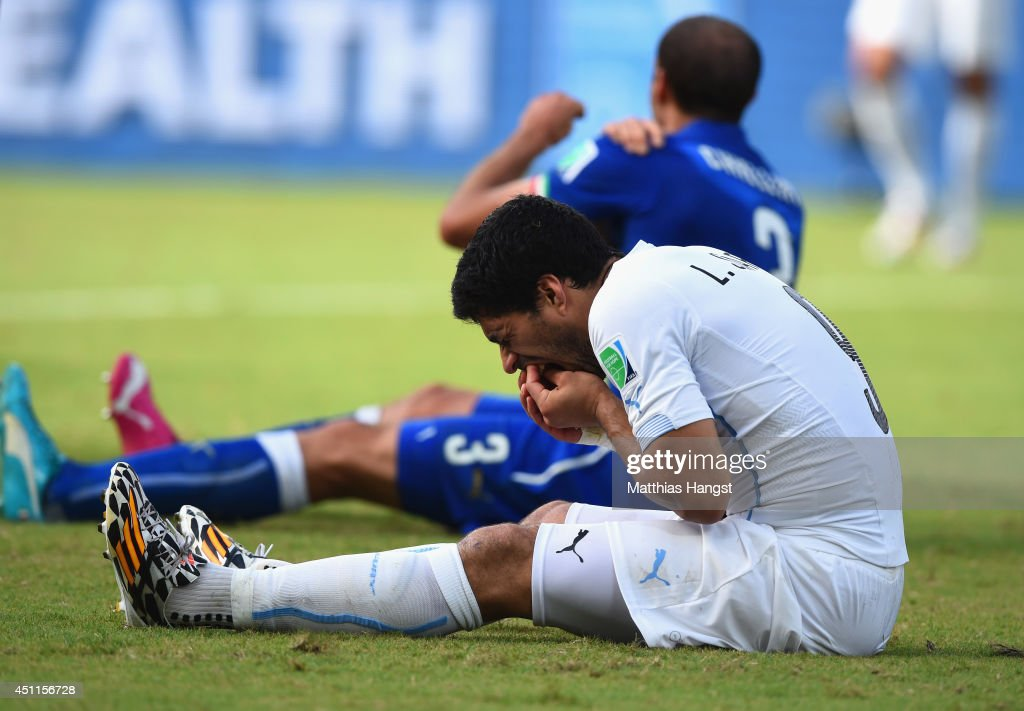 Luis Suarez of Uruguay and Giorgio Chiellini of Italy react after a clash during the 2014 FIFA World Cup Brazil Group D match between Italy and Uruguay at Estadio das Dunas on June 24, 2014 in Natal, Brazil.