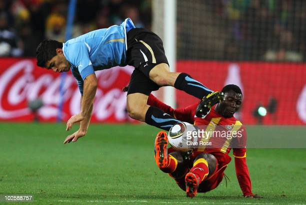 Luis Suarez of Uruguay and Kwadwo Asamoah of Ghana challenge for the ball during the 2010 FIFA World Cup South Africa Quarter Final match between...