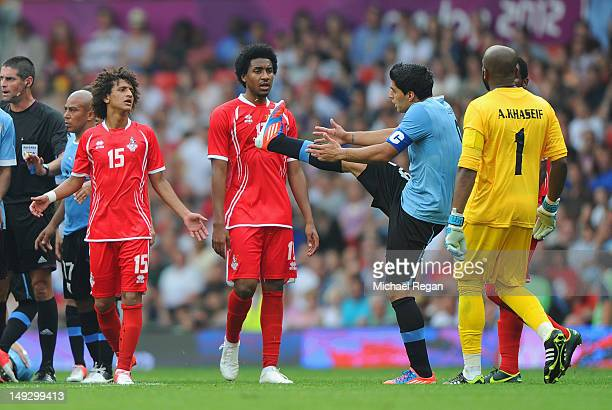 Luis Suarez of Uruguay argues with Omar Abdulrahman and Khamis Esmaeel of the UAE during the Men's Football first round Group A Match of the London...