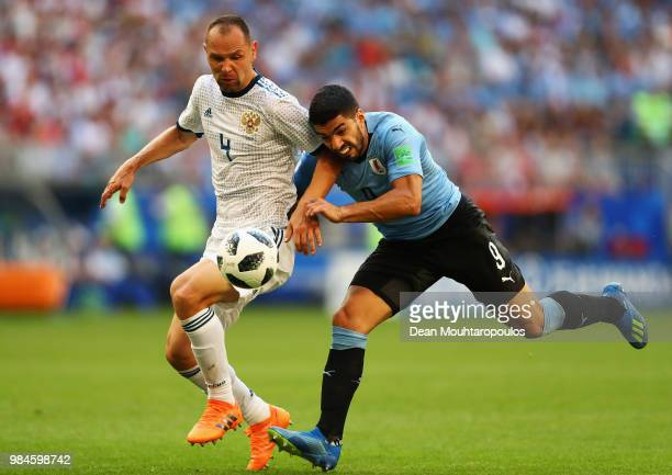 Luis Suarez of Uruguay battles for the ball with Sergey Ignashevich of Russia during the 2018 FIFA World Cup Russia group A match between Uruguay and...