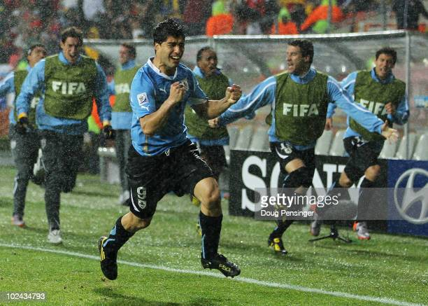 Luis Suarez of Uruguay celebrates scoring his second goal in the driving rain during the 2010 FIFA World Cup South Africa Round of Sixteen match...