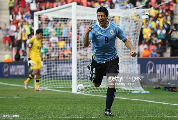 Luis Suarez of Uruguay celebrates scoring the opening goal as Jung Sung-Ryong of South Korea looks dejected during the 2010 FIFA World Cup South...