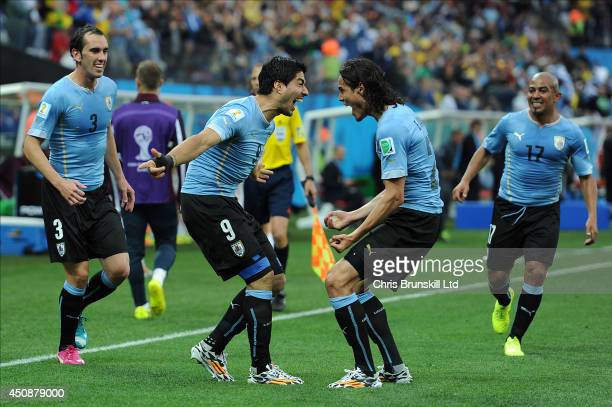 Luis Suarez of Uruguay celebrates scoring the opening goal with teammate Edinson Cavani during the 2014 FIFA World Cup Brazil Group B match between...
