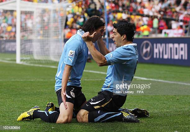 Luis Suarez of Uruguay celebrates scoring with teammate Edinson Cavani during the 2010 FIFA World Cup South Africa Round of Sixteen match between...