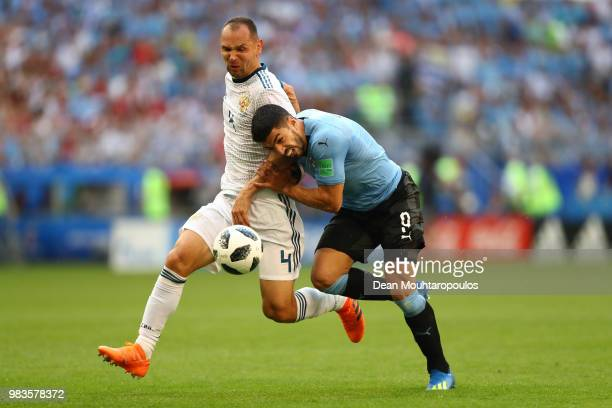 Luis Suarez of Uruguay challenge for the ball with Sergey Ignashevich of Russia during the 2018 FIFA World Cup Russia group A match between Uruguay...