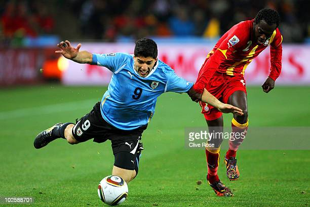 Luis Suarez of Uruguay falls under the challenge of Hans Sarpei of Ghana during the 2010 FIFA World Cup South Africa Quarter Final match between...