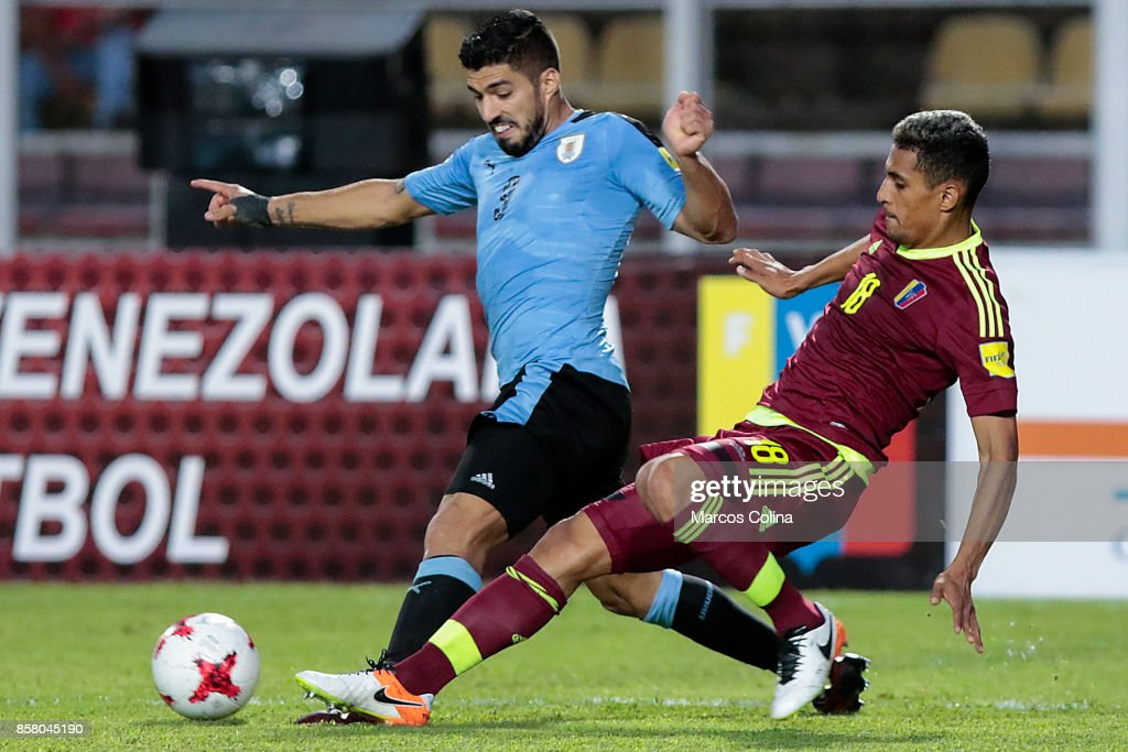Luis Suarez of Uruguay fights for the ball with Victor Garcia of Venezuela during a match between Venezuela and Uruguay as part of FIFA 2018 World Cup Qualifiers at Pueblo Nuevo Stadium on October 05, 2017 in San Cristobal, Venezuela.