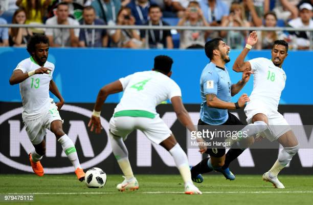 Luis Suarez of Uruguay goes to ground after a tackle from Salem Aldawsari of Saudi Arabia during the 2018 FIFA World Cup Russia group A match between...