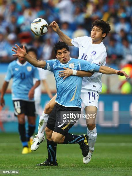 Luis Suarez of Uruguay is challenged by Lee Jung-Soo of South Korea during the 2010 FIFA World Cup South Africa Round of Sixteen match between...