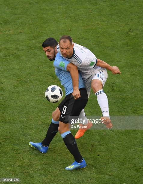 Luis Suarez of Uruguay is challenged by Sergey Ignashevich of Russia during the 2018 FIFA World Cup Russia group A match between Uruguay and Russia...