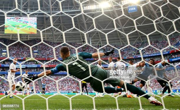 Luis Suarez of Uruguay scores past Igor Akinfeev of Russia his team's first goal during the 2018 FIFA World Cup Russia group A match between Uruguay...