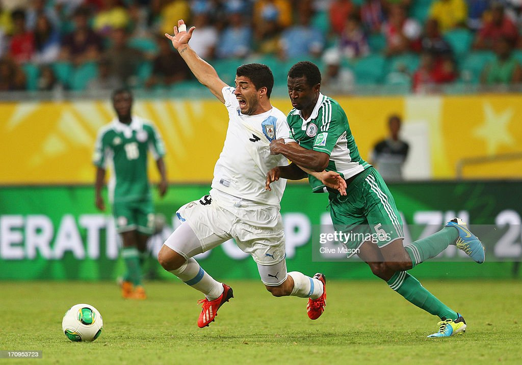 Luis Suarez of Uruguay tangles with Efe Ambrose of Nigeria during the FIFA Confederations Cup Brazil 2013 Group B match between Nigeria and Uruguay at Estadio Octavio Mangabeira (Arena Fonte Nova Salvador) on June 20, 2013 in Salvador, Brazil.