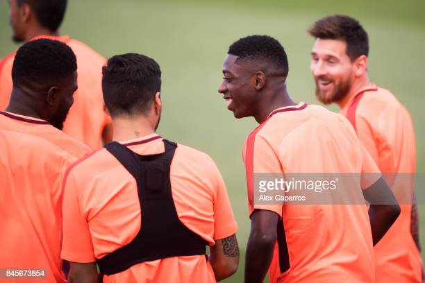 Luis Suarez Ousmane Dembele and Lionel Messi of FC Barcelona enter the pitch before a training session ahead of the UEFA Champions League Group D...