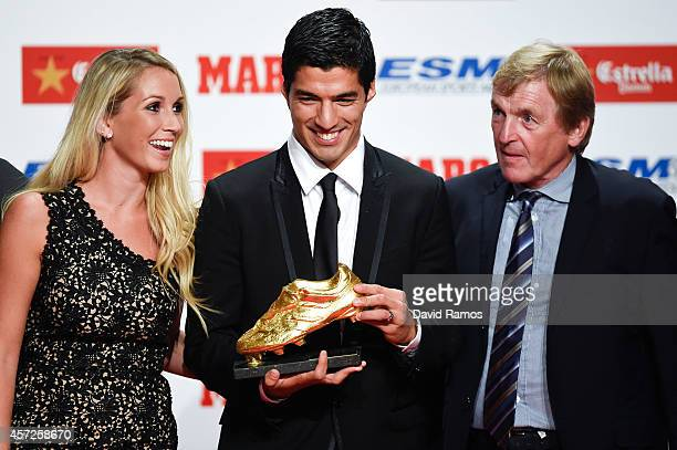 Luis Suarez poses with the Goden Boot Trophy as the best goal scorer in all European Leagues last season next to his wife Sofia Balbi and Kenny...