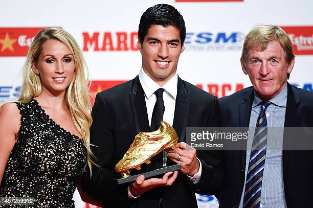 Luis Suarez poses with the Goden Boot Trophy as the best goal scorer in all European Leagues last season with his wife Sofia Balbi and Kenny Dalglish...