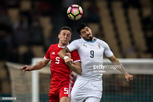 Luis Suarez right of Uruguay national football team heads the ball to make a pass against James Chester of Wales national football team in their...