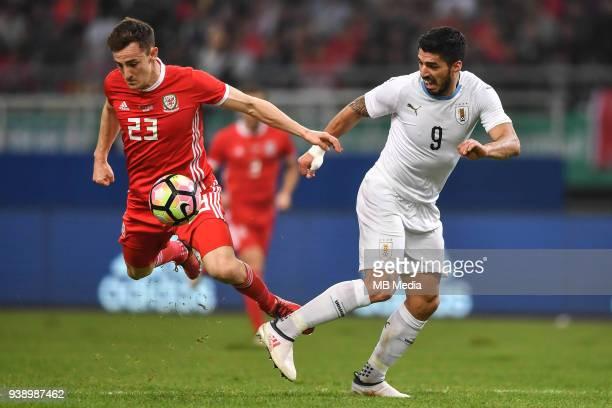 Luis Suarez right of Uruguay national football team kicks the ball to make a pass against Tom Lockyer of Wales national football team in their final...