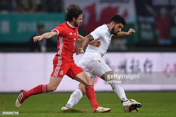 Luis Suarez right of Uruguay national football team kicks the ball to make a pass against Joe Allen of Wales national football team in their final...